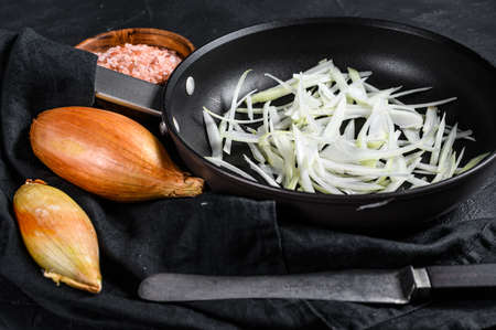 Sliced shallot in a pan, cooking fried onions. Black background. Top view.