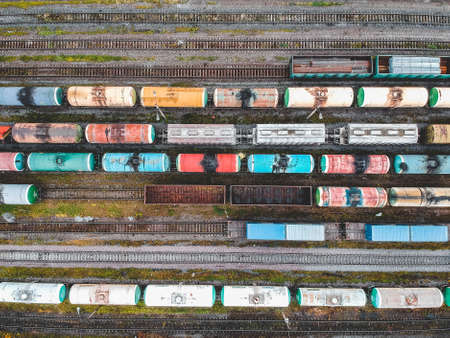 Cargo trains. Aerial view of colorful freight trains on the railway station. Wagons with goods on railroad. Heavy industry. Industrial conceptual scene with trains. View from flying drone. Russia, St. Petersburg. Stock Photo