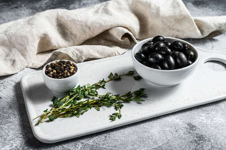 Black pitted olives on a white chopping Board. Gray background. Top view. Banco de Imagens