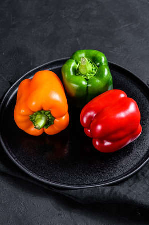 Green, orange and red bell peppers on a black plate. Black background. Top view. Space for text Imagens