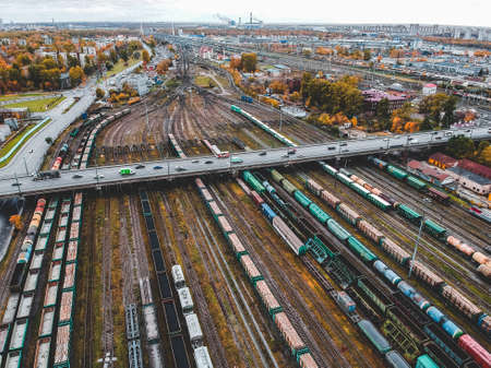 Cargo trains. Aerial view of colorful freight trains on the railway station. Wagons with goods on railroad. Heavy industry. Industrial conceptual scene with trains. View from flying drone. Russia, St. Petersburg.