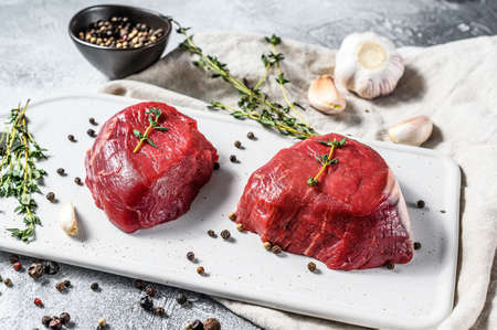 Marble beef tenderloin. Raw filet Mignon steak on a white chopping Board. Gray background. Top view.