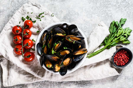 Mussels with herbs and sauce in bowl. Gray background. Top view.