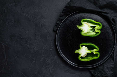 Cut green bell pepper, two halves. Black background. Top view. Space for text sweet pepper, two halves. Black background. Top view. Space for text Reklamní fotografie