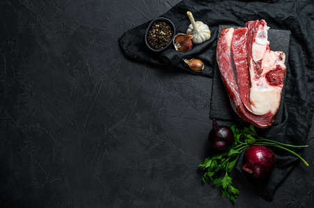 Raw beef with bone on black background. Top view. Space for text. Banco de Imagens