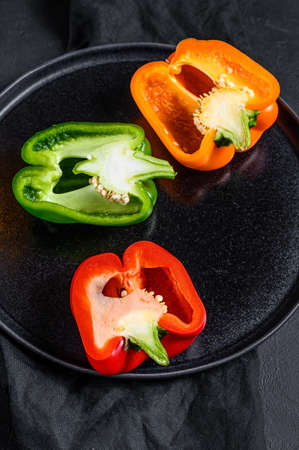Three cut orange, green and red bell peppers. Black background. Top view.