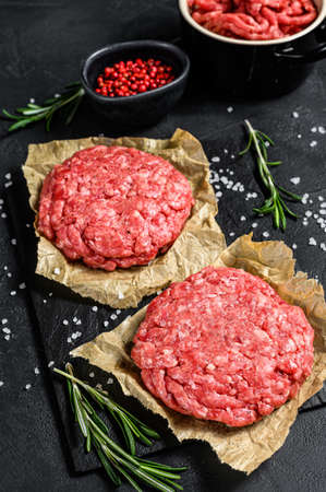 Ground raw meat patties. Meat patties ready to cook. Barbecue party. Farm organic meat. Black background. Top view. 스톡 콘텐츠