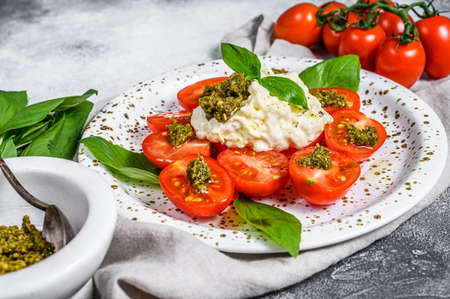 Italian cheese stracciatella (mozzarella buffalo) on small plate served with fresh tomatoes and basil. Gray background. Space for text.