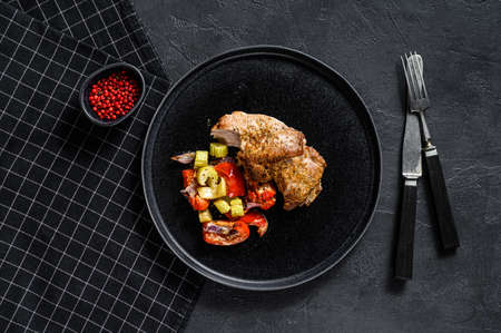 Baked Turkey thigh with vegetables. Black background. Top view. Space for text.
