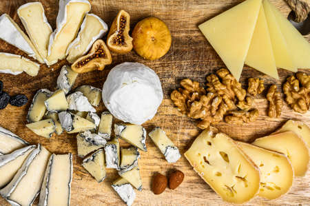 Cheese platter with French organic cheeses, figs, nuts on Gray background. Top view. Tasty cheese starter. Stock Photo