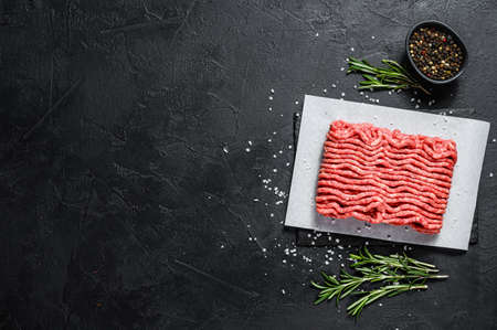 Minced marble beef. Black background. Top view. Space for text.