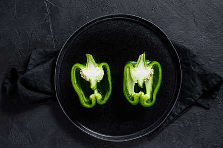 Cut green bell pepper, two halves. Black background. Top view. Space for text 免版税图像