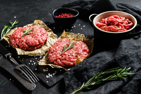 Raw Ground beef meat Burger steak cutlets and seasonings. Farm organic meat. Black background. Top view. 스톡 콘텐츠