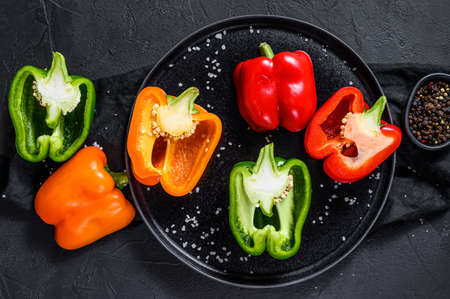 Halves of sliced orange, green and red sweet peppers. Black background. Top view. Space for text. 免版税图像