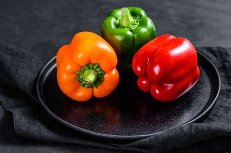 Green, orange and red bell peppers on a plate. Black background. Top view. Standard-Bild