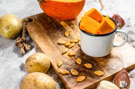 The concept of cooking pumpkin soup. Pumpkin pieces, potatoes, garlic, pumpkin seeds. Cream soup. Gray background. Vegetarian cuisine.