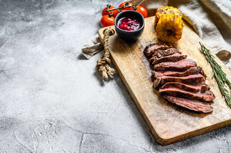 Sliced grilled filet Mignon steak on a wooden chopping Board. Beef tenderloin. Gray background. Top view. Space for text.