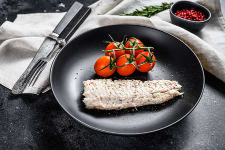 Steamed cod fillet with cherry tomatoes. Black background. Top view.