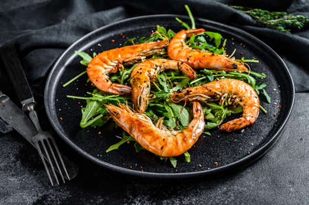 Grilled giant prawns, shrimps, arugula and spices. Black background. Top view.