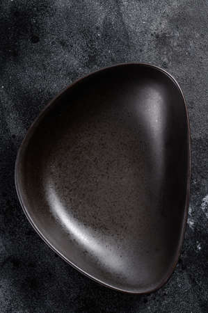 Black plate triangular shape on textured black background. Top view. Copy space.