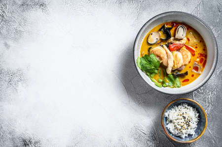 Tom Yum soup with shrimps and coconut milk. Gray background. Top view. Copy space.