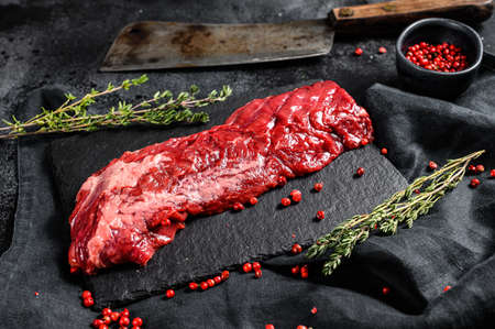 Raw skirt, machete steak with pink pepper and thyme. Black background. Top view. Archivio Fotografico