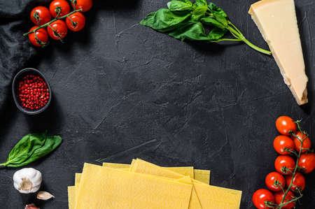 The concept of cooking lasagna. Ingredients, lasagna sheets, Basil, cherry tomatoes, Parmesan, garlic, pepper. Black background. Top view. Space for text.