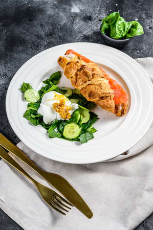 Croissant sandwich with salted salmon served with fresh salad leaves spinach, egg and vegetables.