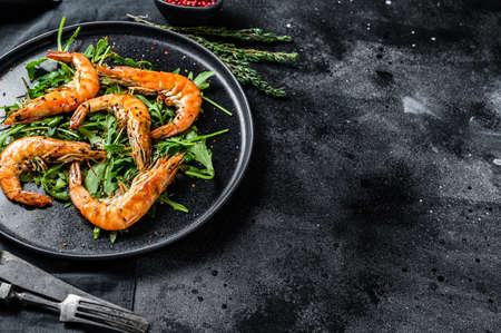 Grilled giant prawns, shrimps, arugula and spices. Black background. Top view. Copy space.