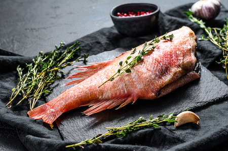 Raw red sea perch on a stone Board with thyme. Black background. Top view