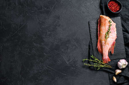 Raw red sea bass on a stone Board with thyme. Black background. Top view. Space for text Foto de archivo
