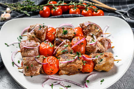 Pork kebab on skewers with tomato and pepper. Food for a picnic. Gray background. Top view