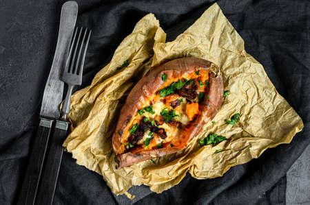 Baked yam, stuffed with cheese and bacon. Organic sweet potato. Black background. Stock Photo
