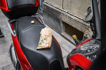 The seat of a scooter with garbage parked on the street. 03.01.2020 Barcelona, Spain.