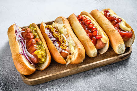 Hot dogs fully loaded with assorted toppings on a tray. Delicious hot-dogs with pork and beef sausages. White background. Top view Foto de archivo