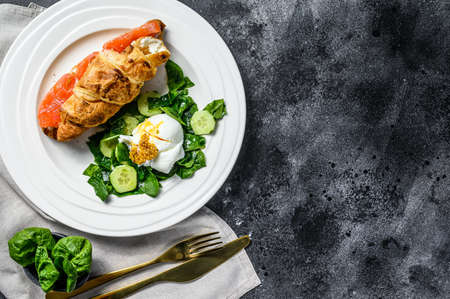 Croissant sandwich with salted salmon served with fresh salad leaves spinach, egg and vegetables. Black background. Top view. Copy space.