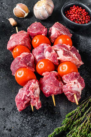Raw pork shish kebab. BBQ meat with tomato and spices. Black background. Top view.