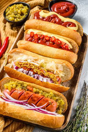 Hot dogs with assorted toppings. Delicious hot-dogs with pork and beef sausages. White background. Top view. Foto de archivo