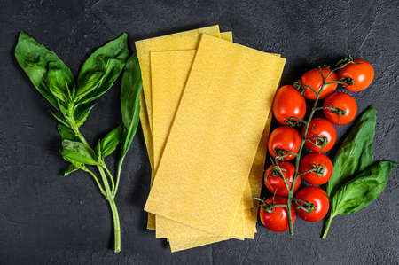 Raw lasagna sheets. Ingredients Basil, cherry tomatoes. Black background. Top view. Space for text.