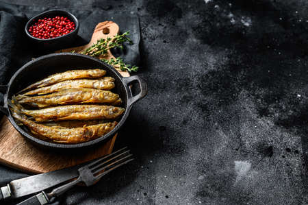 Whole fried battered capelin fish served on a metal skillet. Black background. Top view. Copy space. Stock Photo