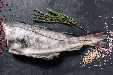 Fresh haddock fish carcass. Black background. Top view.