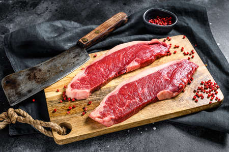 Sirloin steak on a cutting Board. Organic beef meat. Black background. Top view.