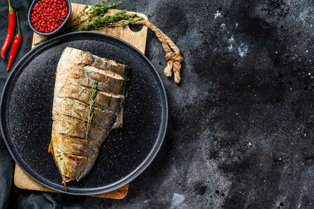 Grilled Yellowtail, Japanese amberjack fillet on a plate. Black background. Top view. Copy space.