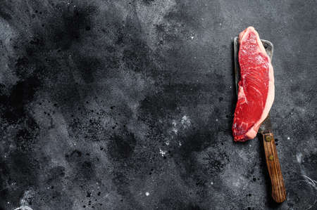 Raw sirloin steak on a cleaver. Marble beef. Black background. Top view. Copy space.