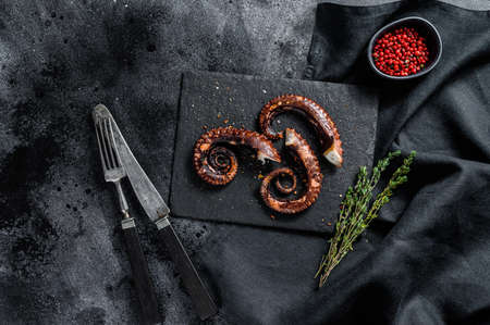 Grilled octopus tentacles. Fresh seafood. Black background. Top view.