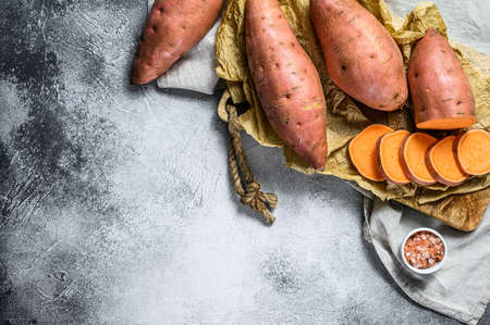 Raw sweet potatoes on a chopping Board, organic yam. Farm vegetables. Gray background. Space for text. Reklamní fotografie