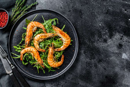 Salad with grilled giant langoustine shrimp, prawns and arugula. Black background. Top view. Copy space. Stock Photo