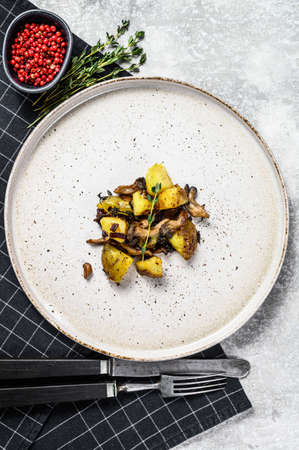 Warm salad with oyster mushrooms and potatoes. Gray background. Top view.