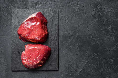 raw steaks fillet Mignon prepared for cooking. Beef tenderloin. Black background. Top view. Space for text. Stock Photo