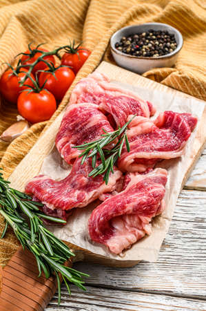 Beef bacon, marbled meat strips on a cutting board. White wooden background. Top view.
